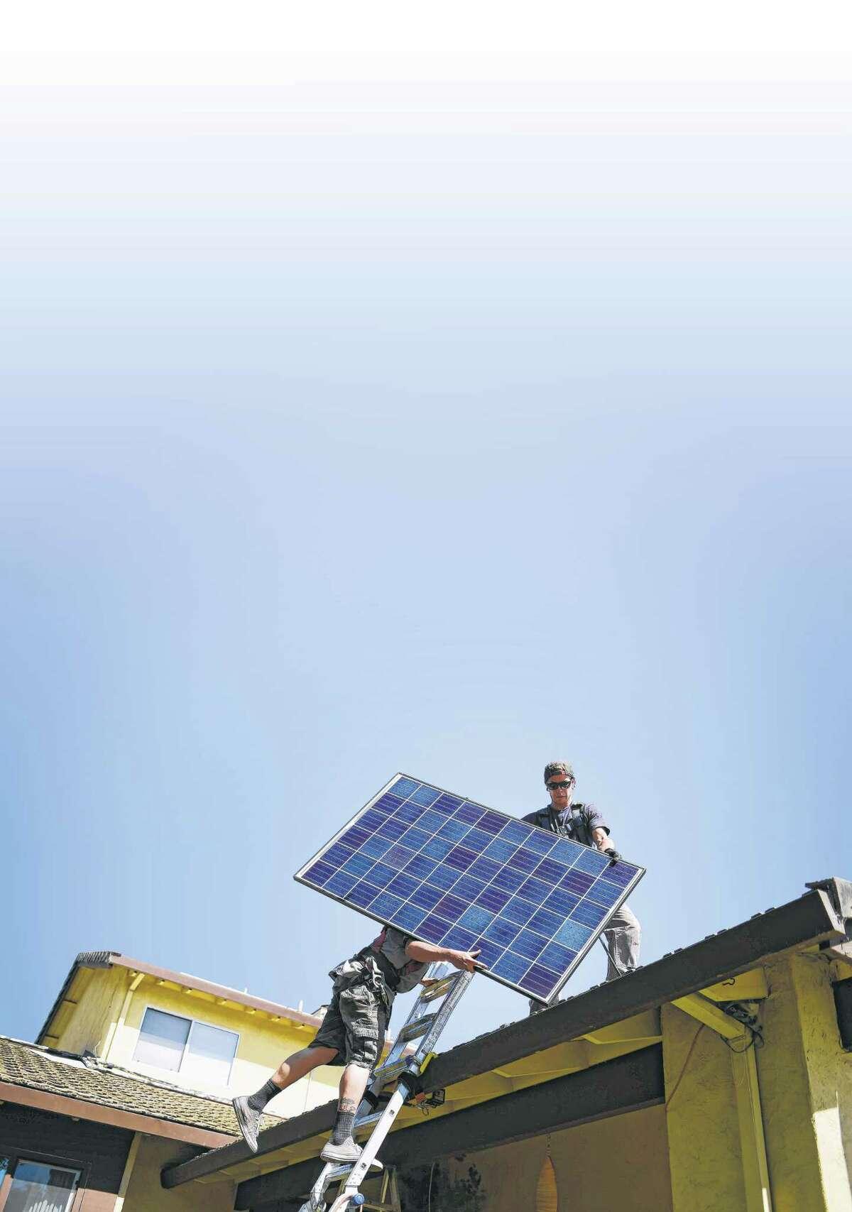 SunRun's Brandon Anderson and Will LaRocque prepare to install a solar panel on a house in Sunnyvale, Calif.