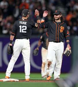 San Francisco Giants' Joe Panik high fives Brandon Crawford after Giants' 2-1 win over Oakland Athletics in Game 2 of Bay Bridge Series at AT&T Park in San Francisco, Calif., on Friday, March 31, 2017.