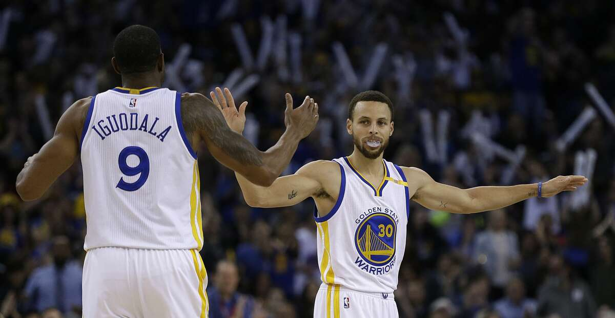 Golden State Warriors' Stephen Curry, right, celebrates a score with Andre Iguodala (9) during the second half of an NBA basketball game against the Houston Rockets Friday, March 31, 2017, in Oakland, Calif. Warriors won 107-98. (AP Photo/Ben Margot)