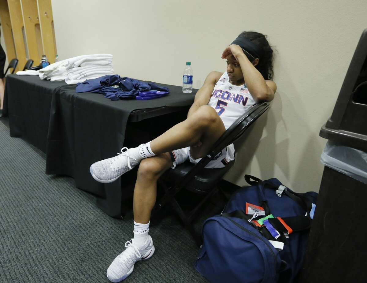Connecticut guard Crystal Dangerfield (5) sits in the locker room after the team's loss to Mississippi State in an NCAA college basketball game in the semifinals of the women's Final Four, Saturday, April 1, 2017, in Dallas. Mississippi State won 66-64. (AP Photo/Tony Gutierrez)