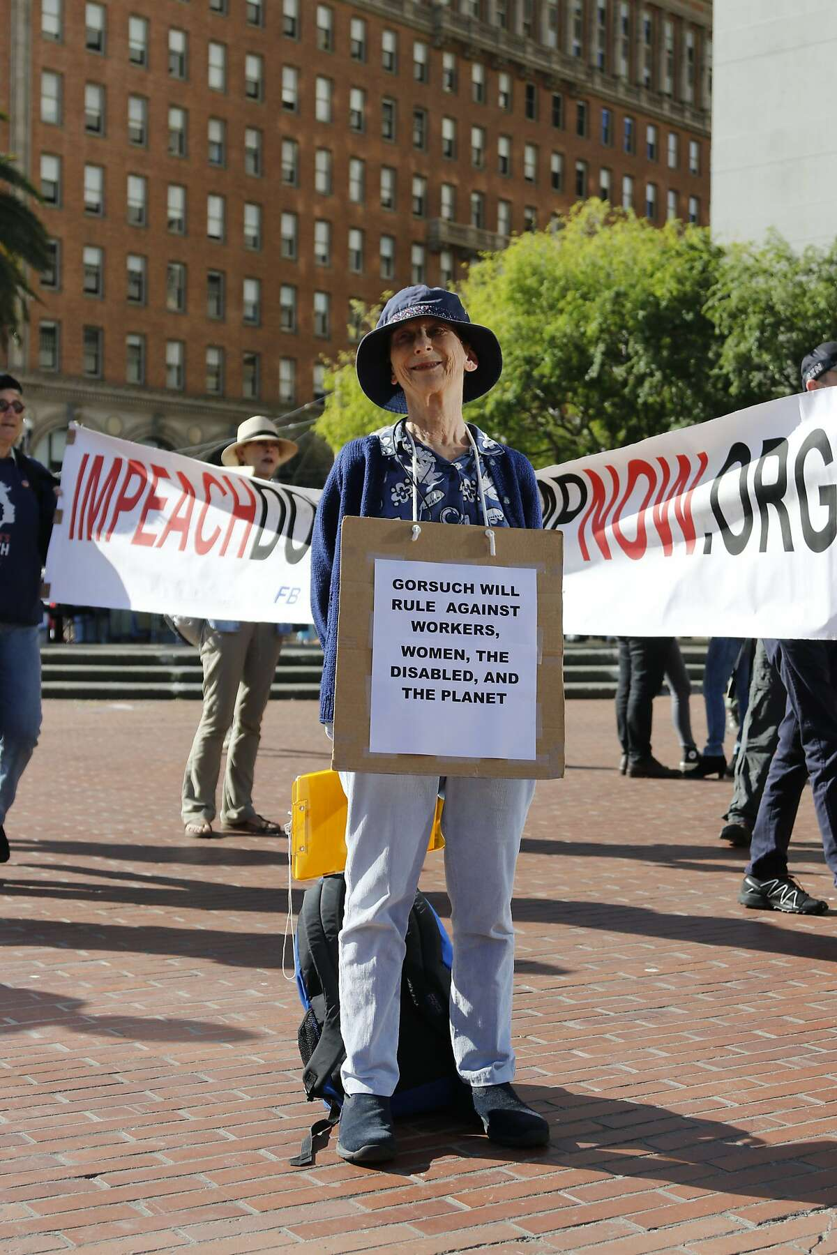Zipporah Collins, 77, of Berkeley wears a sign at a rally in Justin Herman Plaza in San Francisco on Saturday, April 1, 2017. About 100 people attended this event organized by the People's Defense campaign.