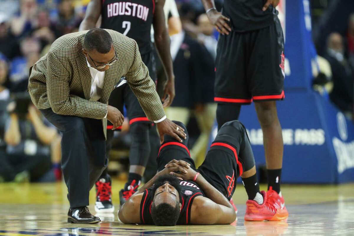 James Harden is tended to after suffering a mishap in the Rockets' loss to the Warriors on Friday night at Oracle Arena in Oakland, Calif. Harden has been hampered by a bothersome injury to his left wrist.