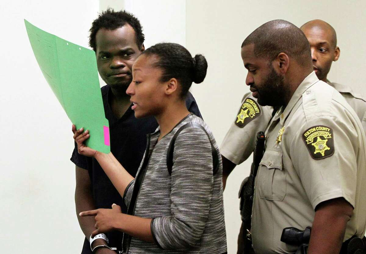 Basil Eleby is escorted by his public defender at the Fulton County Jail in Atlanta on Saturday. Eleby, accused of starting a raging fire that collapsed a portion of Interstate 85 a few miles north of downtown Atlanta, was charged with arson.