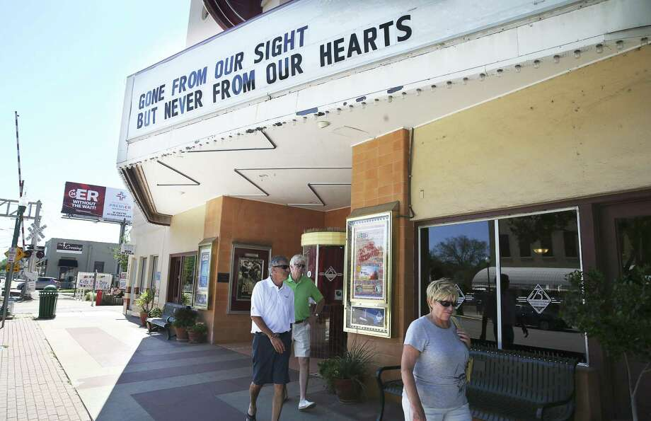 Pedestrians walk by the Brauntex Theatre as it displays a remembrance of the New Braunfels First Baptist Church crash victims. Photo: Tom Reel / San Antonio Express-News / 2017 SAN ANTONIO EXPRESS-NEWS