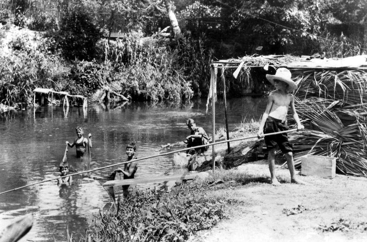 A typical summer scene - children playing and fishing in the then undeveloped San Antonio River between 1930 and 1940.
