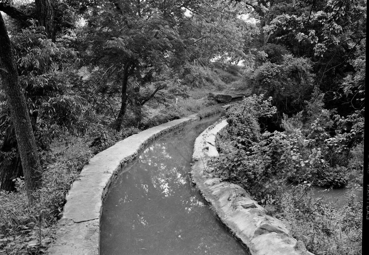 An aqueduct (or acequia) carries water across the San Antonio River.