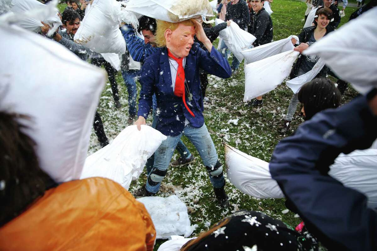 Gus Catalano, wearing a Donald Trump mask, is attacked by pillow-wielding foes during the annual International Pillow Fight Day event Saturday, April 1, 2017, at Cal Anderson Park in Seattle.