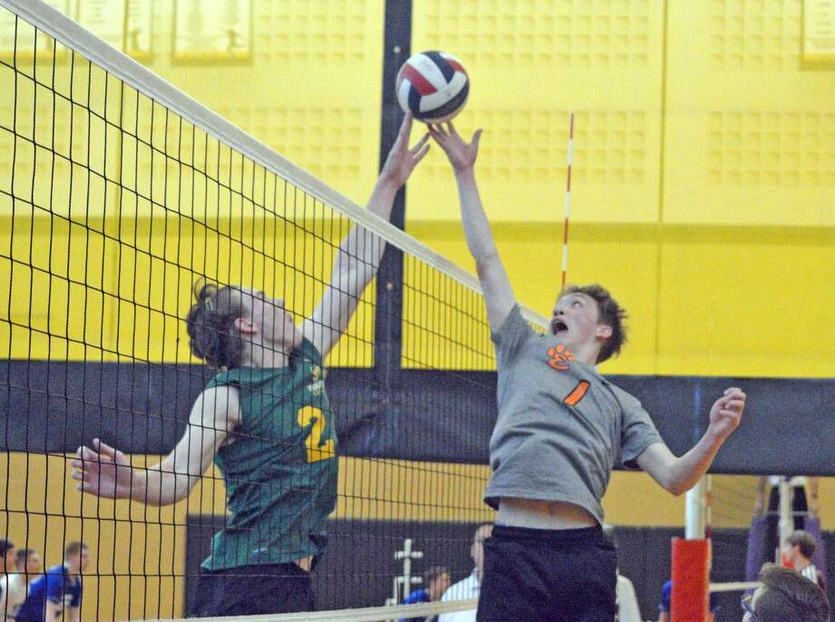 Metro-East Lutheran senior Owen Gusewelle, left, and Edwardsville junior Lucas Verdun go up for the ball at the net during Saturday's first-round match at the Vianney Tournament.
