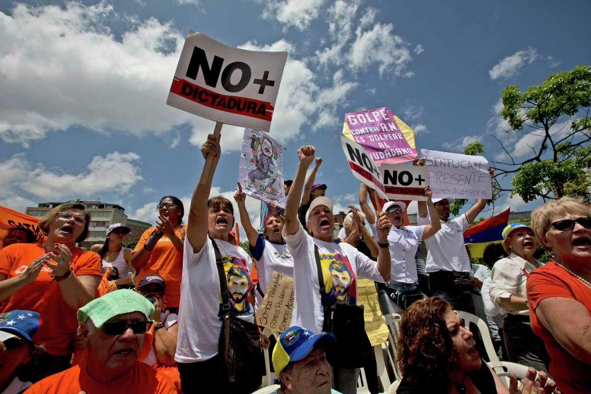 Opposition members shout slogans against Venezuela's President Nicolas Maduro during a National Assembly special session in Caracas, Venezuela, Saturday, April 1, 2017. Venezuela's president and Supreme Court backed down Saturday from an audacious move to strip congress of its legislative powers that had sparked widespread charges that the South American country was no longer a democracy. (AP Photo/Fernando Llano)