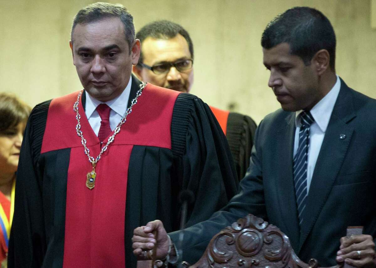 Venezuela's Supreme Court President Maikel Moreno, left, arrives to a meeting with journalist at the Supreme Court in Caracas, Venezuela, Saturday, April 1, 2017. Venezuela's president and Supreme Court backed down Saturday from an audacious move to strip congress of its legislative powers that had sparked widespread charges that the South American country was no longer a democracy. (AP Photo/Ariana Cubillos)