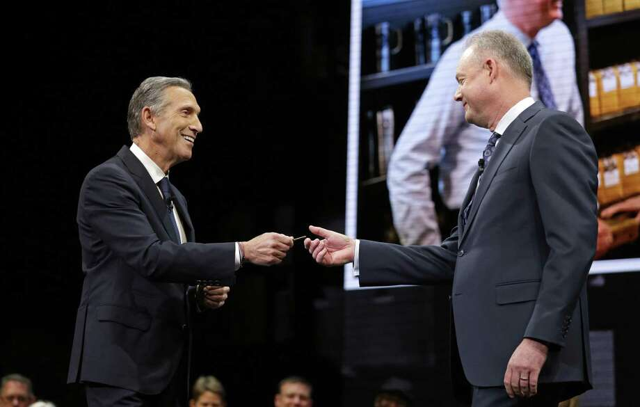 Starbucks CEO Howard Schultz, left, hands over the door key of the Pike Place Market Starbucks' store to President and Chief Operating Officer Kevin Johnson at the company's annual shareholders meeting March 22 in Seattle. Johnson takes over as CEO from Schultz, who will become executive chairman, April 3. Photo: Elaine Thompson /Associated Press / Copyright 2017 The Associated Press. All rights reserved.