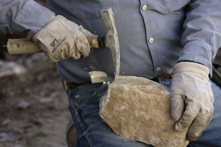 Blas Perez breaks rock as he repairs a limestone border near building 23 at La Villita in 2010. Hand-hewn limestone blocks formed much of San Antonio's early buildings, including the Spanish colonial missions and San Fernando Cathedral. Photo: Jerry Lara /San Antonio Express-News / glara@express-news.net