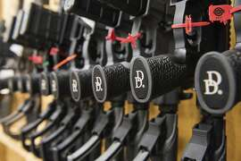 In this March 9, 2017, photo a row of AR-15 style rifles manufactured by Daniel Defense sit in a vault at the company's headquarters in Black Creek, Ga. The company, based in Black Creek, Georgia, and founded in 2001, is one of the industry leaders in the making of long guns in the United States. President Donald Trump promised to revive manufacturing in the U.S., but one sector is poised to shrink under his watch: the gun industry. Fears of limits on guns led to a surge in demand during President Barack Obama's tenure and manufacturers leapt to keep up. (AP Photo/Lisa Marie Pane)