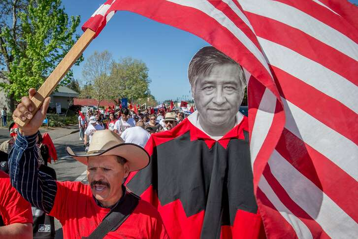 Guadalupe Suarez waves the American flag during a march for Cesar Chavez on Sunday, April 2, 2017, in Santa Rosa, Calif.