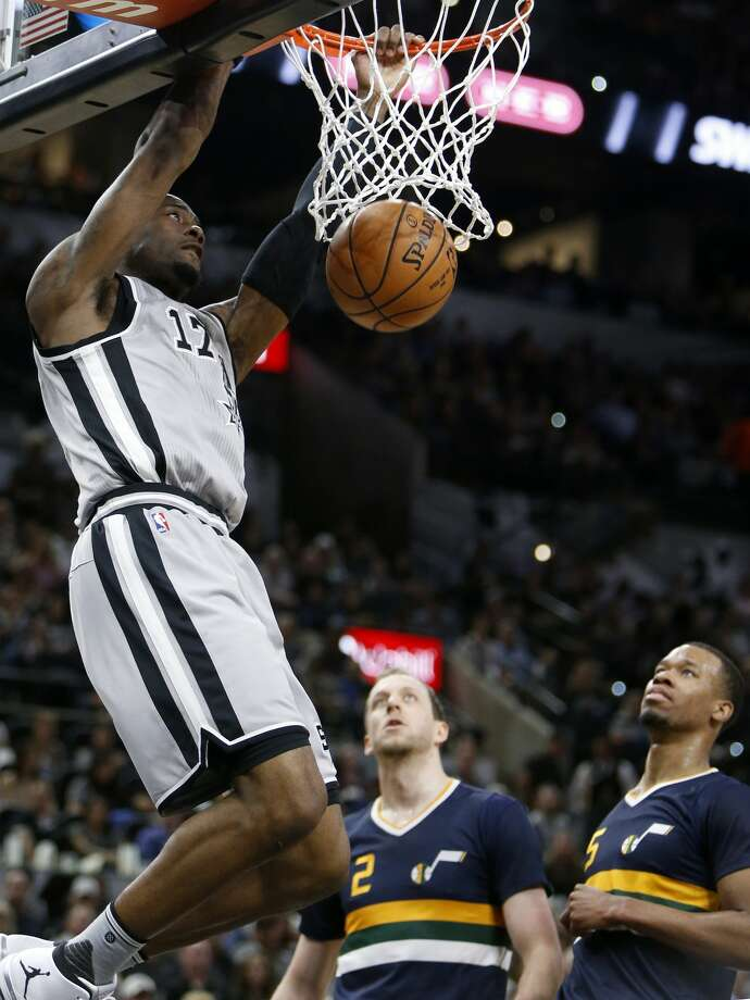 San Antonio Spurs' Jonathon Simmons dunks around Utah Jazz's Joe Ingles (center left) and Rodney Hood during first half action Sunday April 2, 2017 at the AT&T Center. Photo: Edward A. Ornelas/San Antonio Express-News