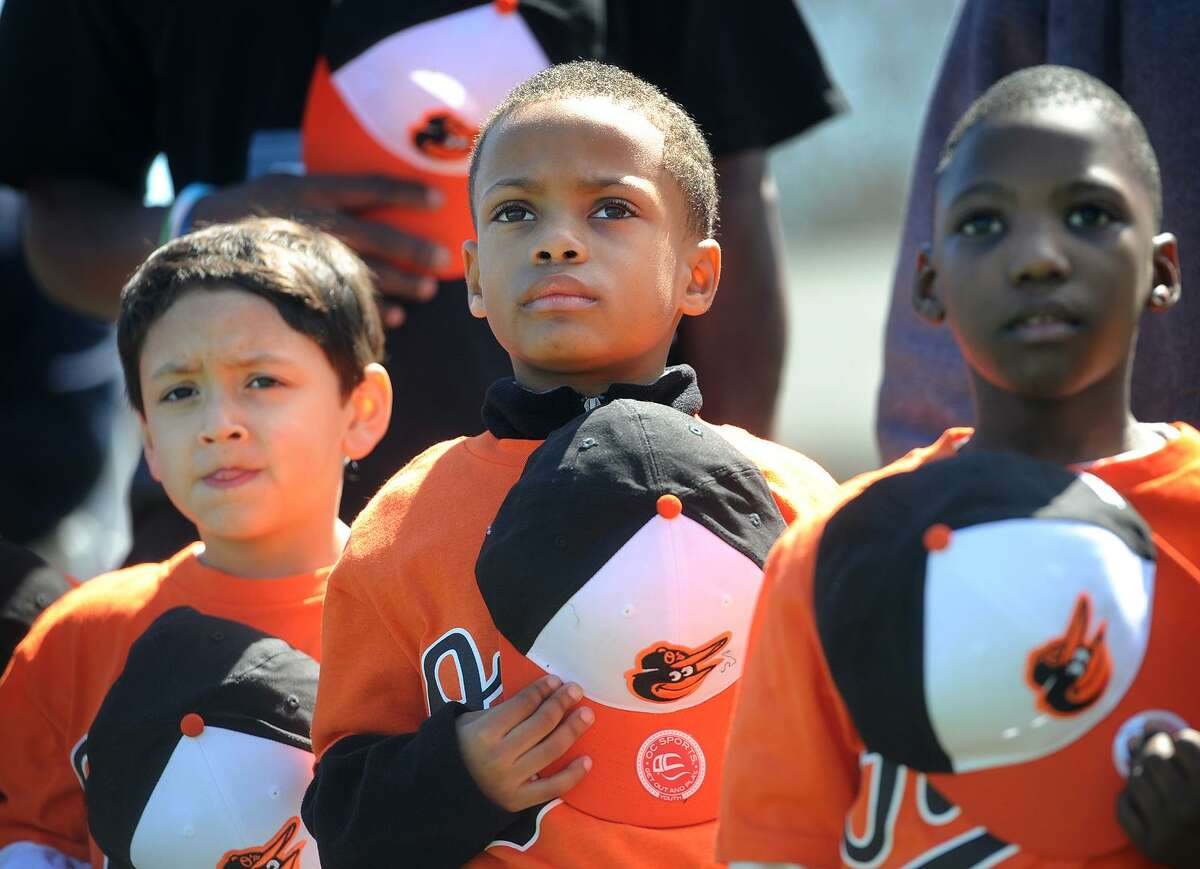 From left; Caleb Green, Alijah Dixon, and Jeremiah Robinson, all 6, of Bridgeport, remove their caps for the singing of the National Anthem during opening day of the North End Little League at their new complex of fields on Thorme Street in Bridgeport, Conn. on Sunday, April 2, 2017.