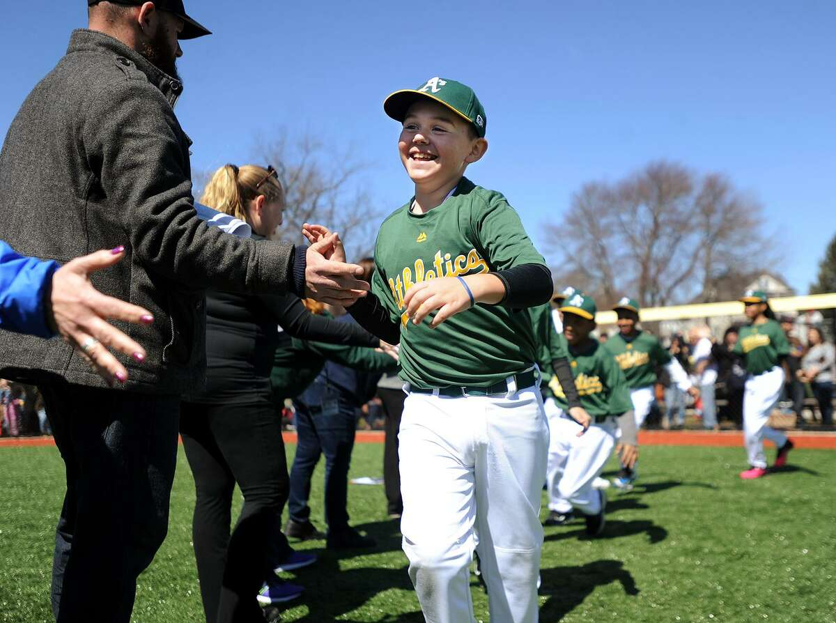Logan Parra, 9, of Bridgeport, leads his teammates on to the field during opening day of the North End Little League at their new complex of fields on Thorme Street in Bridgeport, Conn. on Sunday, April 2, 2017.