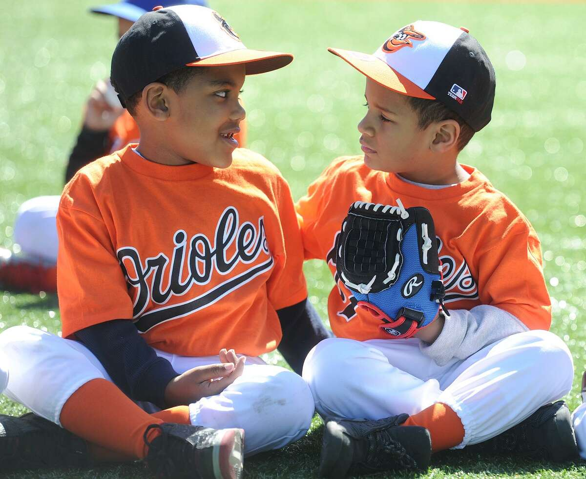 Teammates Tristan King, 6, left, and Kanavis Cole, 5, have a seat on the field during opening day ceremononies for the North End Little League at their new complex of fields on Thorme Street in Bridgeport, Conn. on Sunday, April 2, 2017.