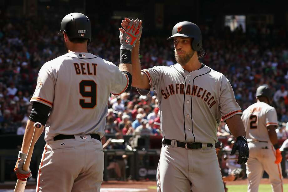 PHOENIX, AZ - APRIL 02:  Madison Bumgarner #40 of the San Francisco Giants high fives Brandon Belt #9 after Bumgarner hit a solo home run against the Arizona Diamondbacks during the fifth inning of the MLB opening day game at Chase Field on April 2, 2017 in Phoenix, Arizona.  (Photo by Christian Petersen/Getty Images) Photo: Christian Petersen, Getty Images