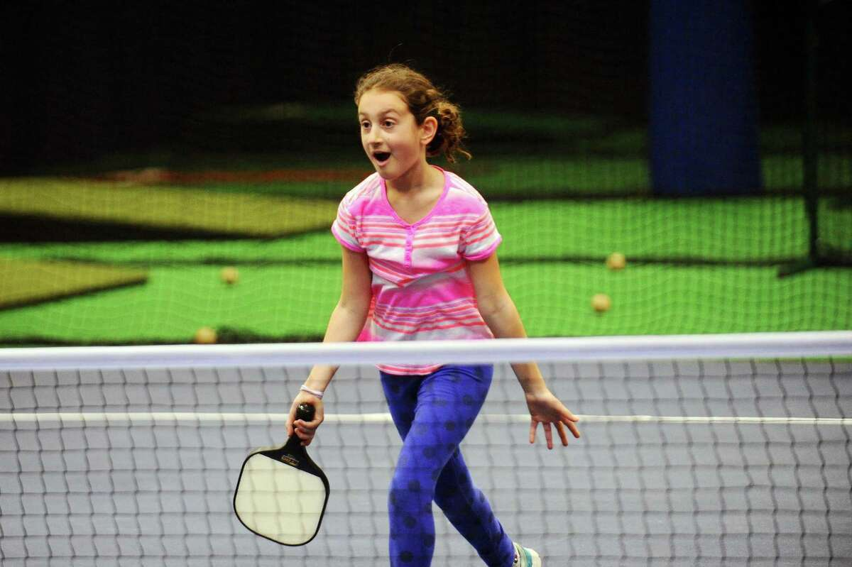 10-year old Sydney Cibilia, of New Canaan, runs the the net to celebrate winning a point during a casual pick-up pickleball game at the grand opening of Bobby Valentine's Sports Academy on Largo Drive in Stamford, Conn. on Sunday, April 2, 2017.