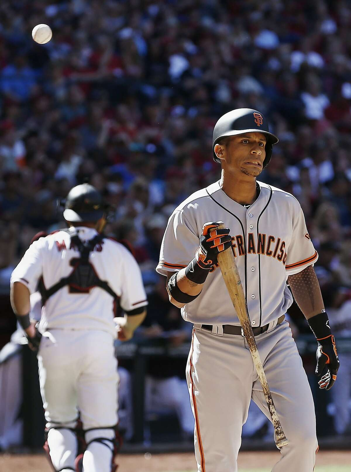 San Francisco Giants' Gorkys Hernandez, right, grimaces after being called out on strikes as Arizona Diamondbacks' Jeff Mathis, left, runs back to the dugout during the sixth inning of an opening day baseball game Sunday, April 2, 2017, in Phoenix. (AP Photo/Ross D. Franklin)