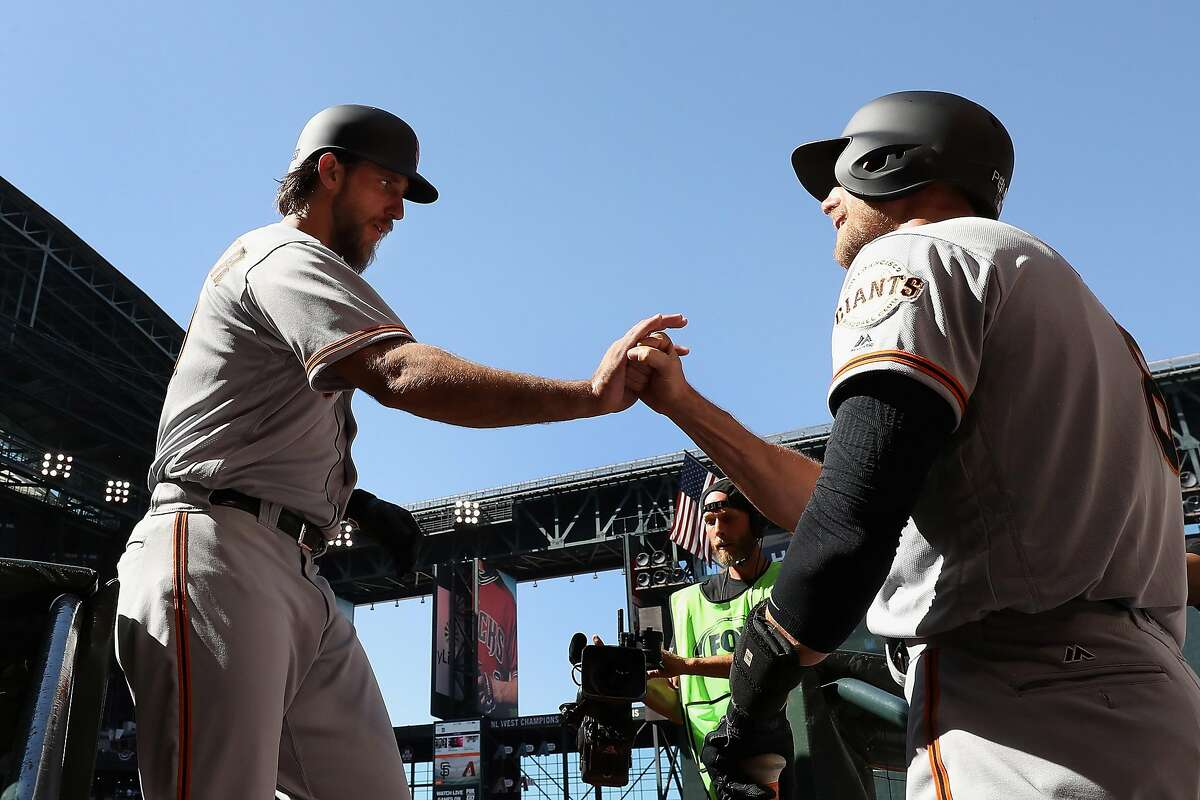 PHOENIX, AZ - APRIL 02: Madison Bumgarner #40 of the San Francisco Giants high fives Hunter Pence #8 after Bumgarner hit a solo home run against the Arizona Diamondbacks during the seventh inning of the MLB opening day game at Chase Field on April 2, 2017 in Phoenix, Arizona. (Photo by Christian Petersen/Getty Images)