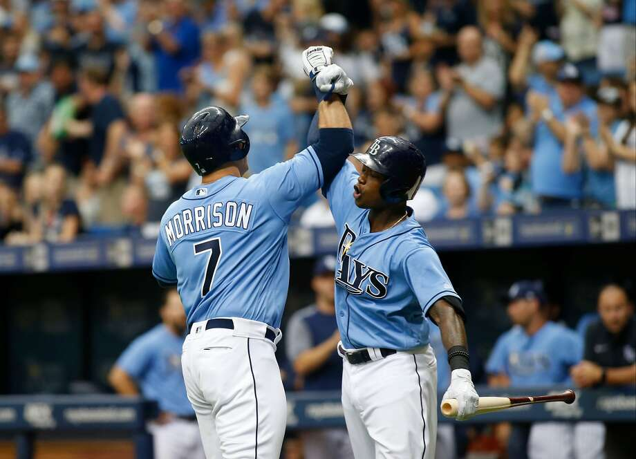 Logan Morrison (7), who had three RBIs, is congratulated by teammate Tim Beckham after hitting a home run off of Yankees ace Masahiro Tanaka. Photo: Brian Blanco, Getty Images