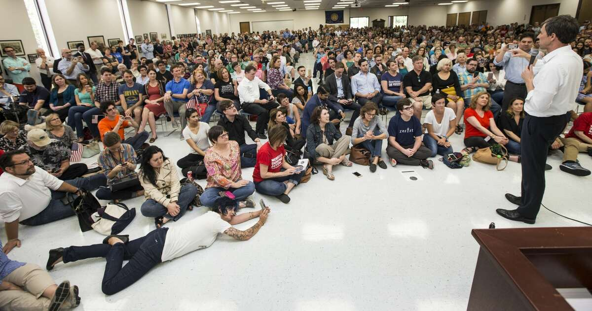A woman lies on the floor using her phone to capture a speech by Rep. Beto O'Rourke, D-Texas, during an April campaign stop in Houston. ( Brett Coomer / Houston Chronicle )