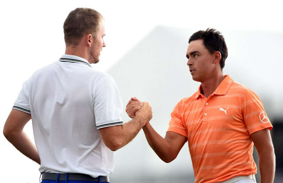 Russell Henley (left) and playing partner Rickie Fowler shake hands after Henley won the Houston Open. Photo: Josh Hedges, Getty Images