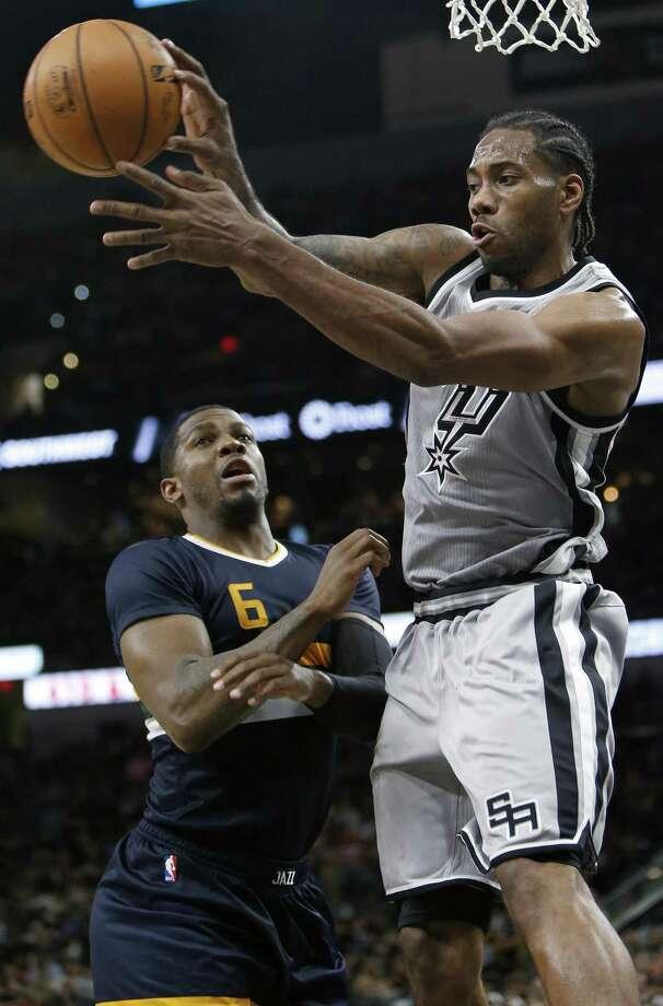 Spurs' Kawhi Leonard passes around the Utah Jazz's Joe Johnson during second half action on April 2, 2017 at the AT&T Center. The Spurs won 109-103. Photo: Edward A. Ornelas /San Antonio Express-News / © 2017 San Antonio Express-News