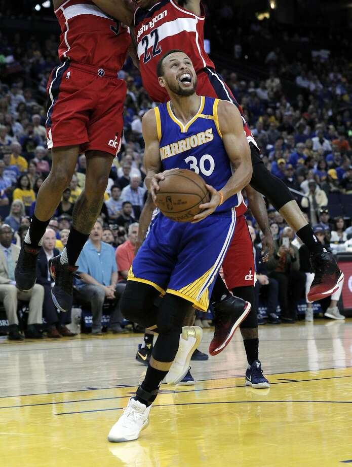 Stephen Curry (30) defended by Bradley Beal (3) and Otto Porter jr. (22) in the first half as the Golden State Warriors played the Washington Wizards , Calif., on Sunday, April 2, 2017. Photo: Carlos Avila Gonzalez, The Chronicle