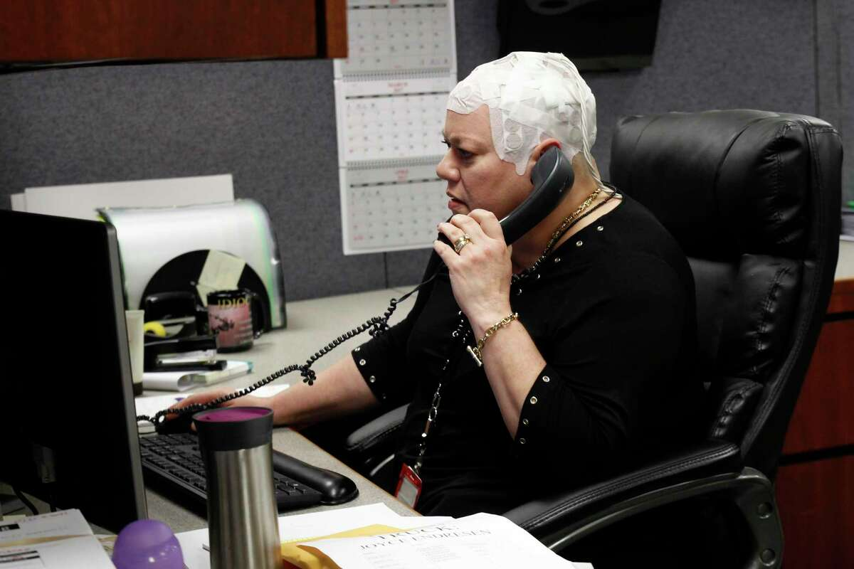 In this March 29, 2017 photo, Joyce Endresen wears an Optune therapy device for brain cancer, as she speaks on a phone at work in Aurora, Ill. She was diagnosed in December 2014 with Glioblastoma. She had two surgeries to remove the tumor as well as radiation and chemotherapy, but is now trying the new therapy that requires her to wear the electrodes on her head as much as possible. They create low intensity electric fields that disrupt cell reproduction, which makes the cells die. (AP Photo/Carrie Antlfinger) ORG XMIT: RPCA103