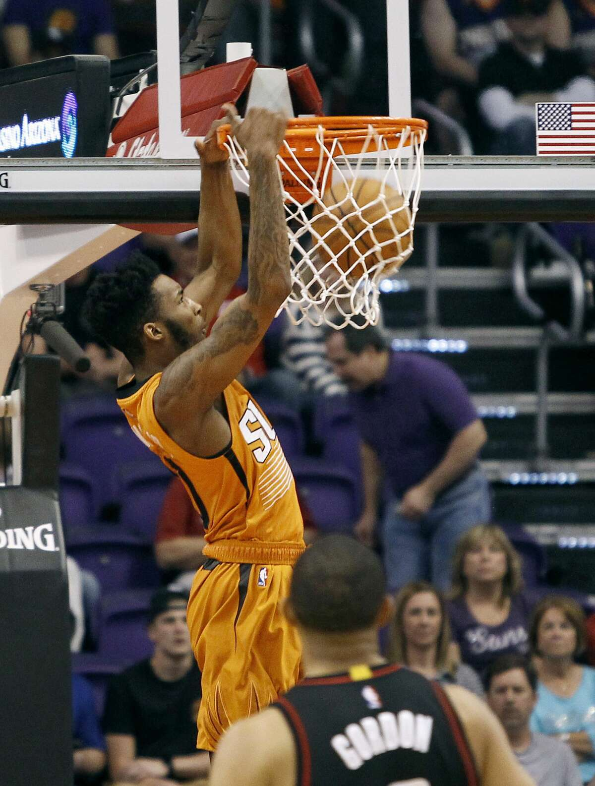 Phoenix Suns' Derrick Jones Jr., top, dunks the ball in front of Houston Rockets' Eric Gordon during the first half of an NBA basketball game, Sunday, April 2, 2017, in Phoenix. (AP Photo/Ralph Freso)