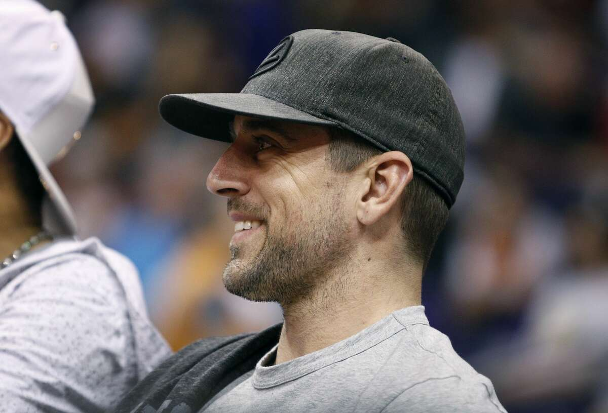 Green Bay Packers quarterback Aaron Rodgers smiles as he watches an NBA basketball game between the Phoenix Suns and the Houston Rockets, Sunday, April 2, 2017, in Phoenix. (AP Photo/Ralph Freso)