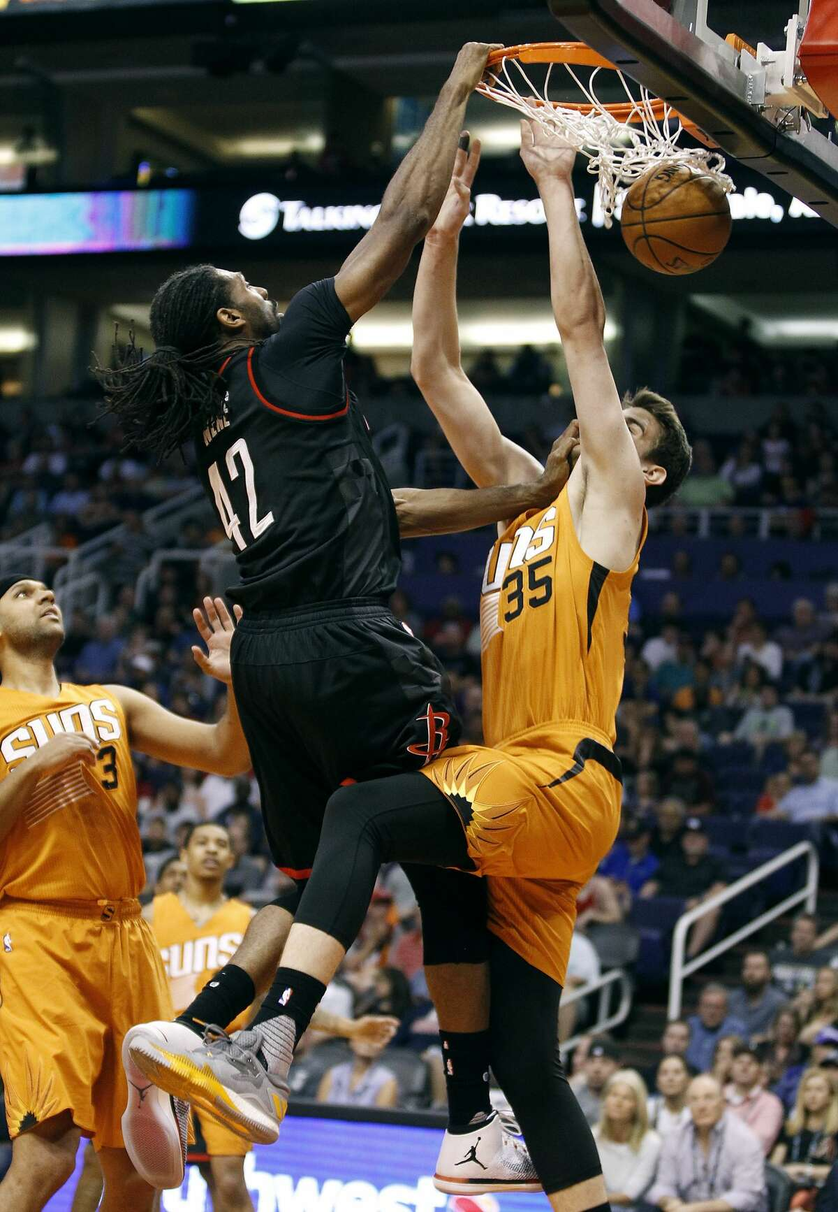 Houston Rockets' Nene (42) dunks over Phoenix Suns' Dragan Bender (35) and Jared Dodley (3) during the first half of an NBA basketball game, Sunday, April 2, 2017, in Phoenix. (AP Photo/Ralph Freso)