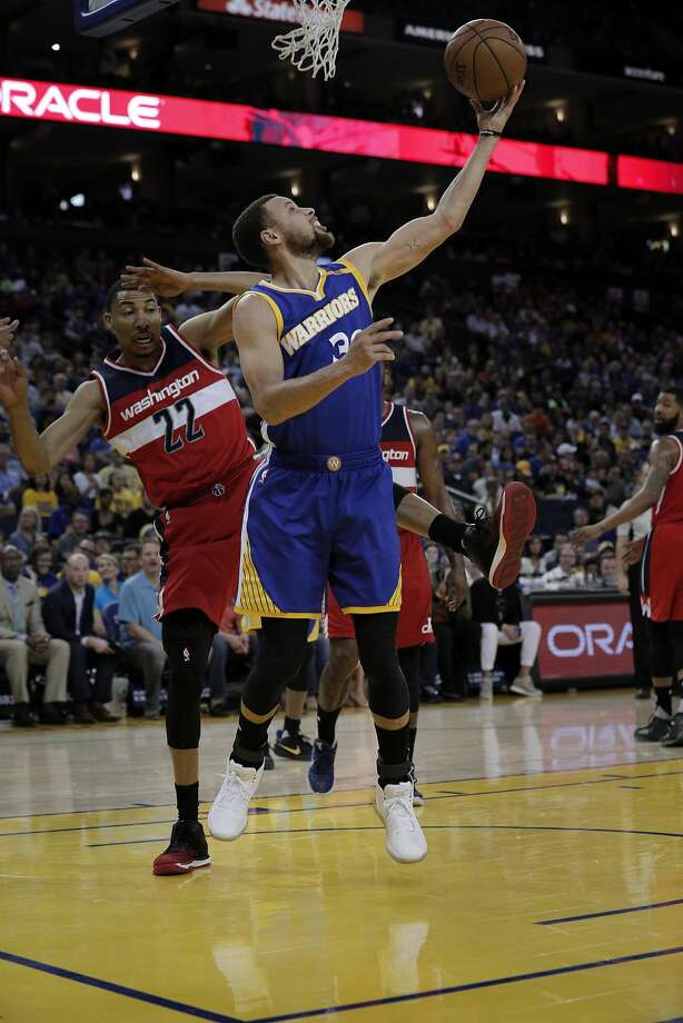 Stephen Curry (30) puts in a reverse layup in the first half as the Golden State Warriors played the Washington Wizards , Calif., on Sunday, April 2, 2017. Photo: Carlos Avila Gonzalez, The Chronicle