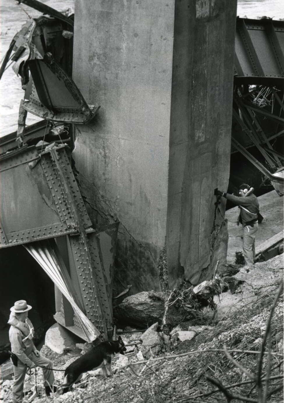 Days after Schoharie Creek Thruway bridge collapse, Trooper Raymond Marshal, left, searches the Schoharie Creek shoreline as Sgt. John Curry, right, uses an audio device to detect for movement in one the bridge supports, April 15, 1987. (Fred McKinney / Times Union archive)