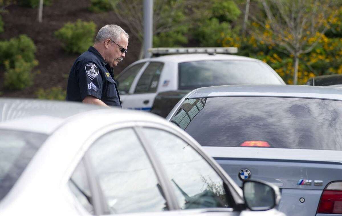 FILE - Stamford Police Department officers pull over and ticket drivers caught texting or talking on cell phones while driving at the intersection of Elm St. and North State Street in Stamford, Conn., on Wednesday, September 3, 2014.