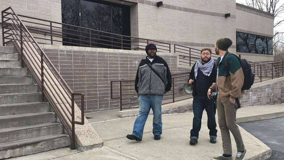 Dominic Ricardo Morgan of Utica, at left, arrives at the federal Immigration and Customs Enforcement office in Colonie Monday. A Jamaican immigrant is scheduled to meet with ICE agents for his monthly check-in soon after. (Emily Masters / Times Union) Photo: Emily Masters / Times Union