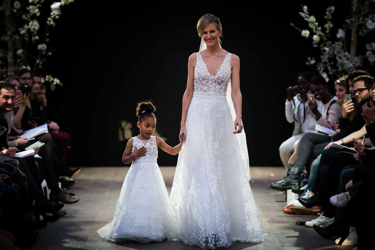 A model and a girl present creations by Cymbeline Wedding Dresses house, on April 1, 2017 in Paris. The Connecticut Better Business Bureau has some tips for negotiating the high costs and high stress of wedding planning. / AFP PHOTO / MARTIN BUREAUMARTIN BUREAU/AFP/Getty Images