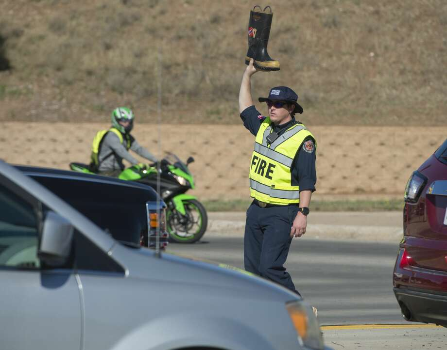 Midland Fire Department's Phillip Koonce walks through traffic April 3, 2017, at the intersection of Loop 250 and Midland Drive collecting donations for Muscular Dystrophy during the annual Fill the Boot campaign. Photo: Tim Fischer/Midland Reporter-Telegram