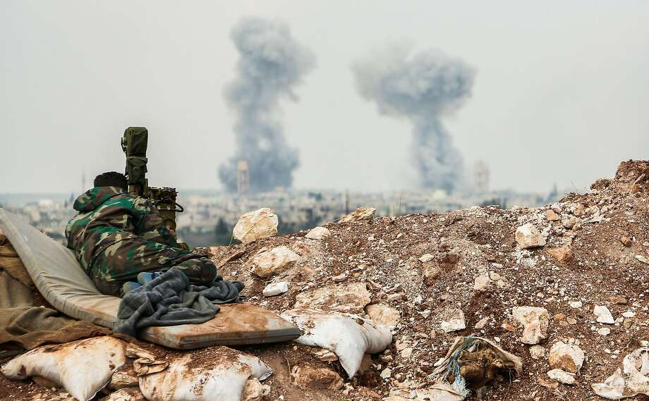 A Syrian government artillery observer watches strikes Saturday in the central province of Hama. Photo: STRINGER, AFP/Getty Images