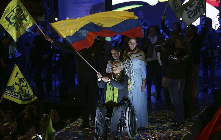 Ruling party candidate Lenin Moreno waves an Ecuadoran flag in Quito as he claims victory Sunday in the presidential election. His rival, Guillermo Lasso, is demanding a recount. Photo: Dolores Ochoa, Associated Press