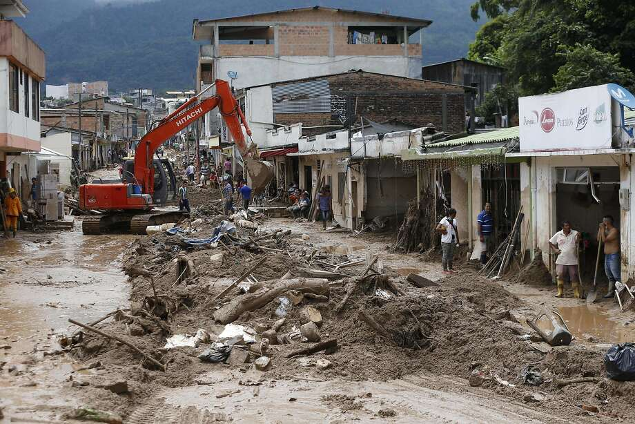 A backhoe removes debris and mud from a street in Mocoa. The city of 40,000 in southern Colombia was devastated by floods. Photo: Fernando Vergara, Associated Press