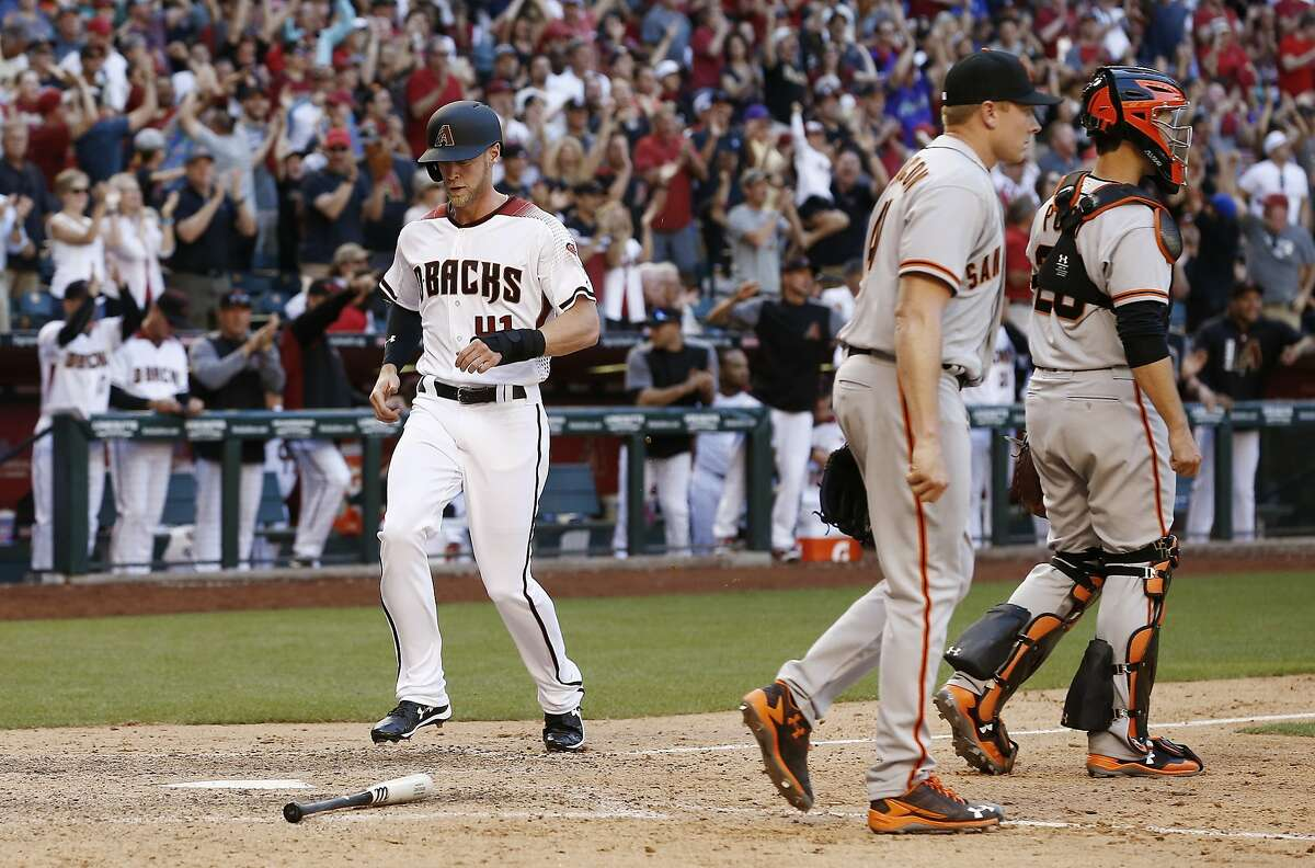 Arizona Diamondbacks Jeremy Hazelbaker, left, scores a run as San Francisco Giants' Mark Melancon, second from right, and catcher Buster Posey, right, walk away from home plate during the ninth inning of an Opening Day baseball game Sunday, April 2, 2017, in Phoenix. The Diamondbacks defeated the Giants 6-5. (AP Photo/Ross D. Franklin)