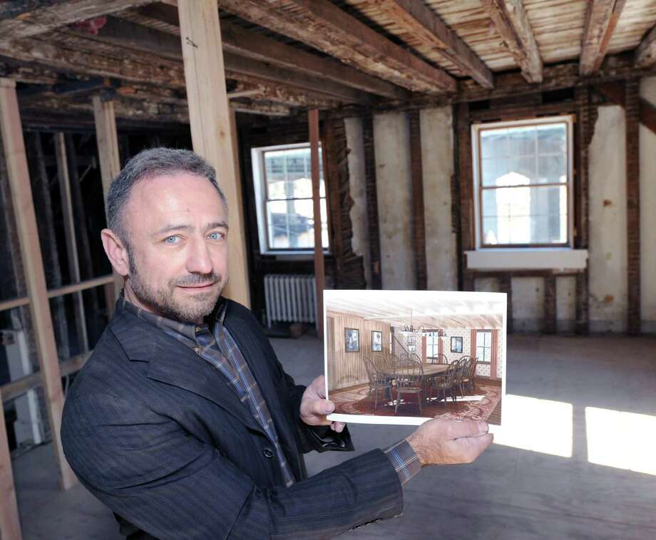 David Scott Parker, the architect who is in charge of renovating and redesigning the historic buidling that will be the new headquarters for the Greenwich Historical Society, holds a rendering of what the interior top floor of the building will look like upon completion while standing in that space after he spoke about the renovating process at the building that is located at the Greenwich Historical Society in the Cos Cob section of Greenwich, Conn., Friday, March 17, 2017. The buidling was once a tavern and a hotel. Photo: Bob Luckey Jr. / Hearst Connecticut Media / Greenwich Time