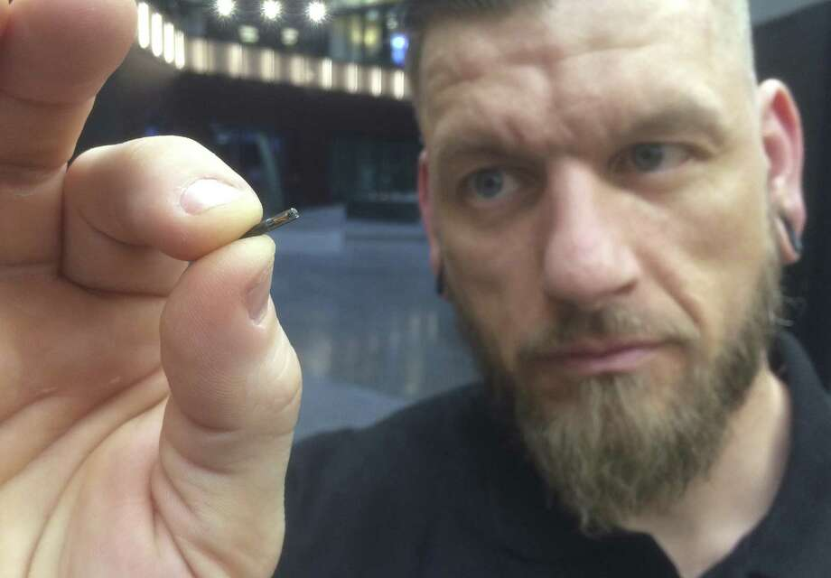 Self-described body hacker Jowan Osterlund from Biohax Sweden, holds a small microchip implant, similar to those implanted into workers at the Epicenter digital innovation business centre during a party at the co-working space in central Stockholm, Tuesday March 14, 2017. Microchips are being implanted into volunteers to help them open doors and operate office equipment, and its become so popular that members of the Epicentre cyborg club hold regular parties for those with the tiny chips embedded in their hands. Photo: James Brooks /Associated Press / AP