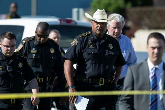 Authorities investigate the scene where Precinct 3 Assistant Chief Deputy Clint Greenwood was fatally shot behind the Baytown Courthouse Monday, April 3, 2017, in Houston.