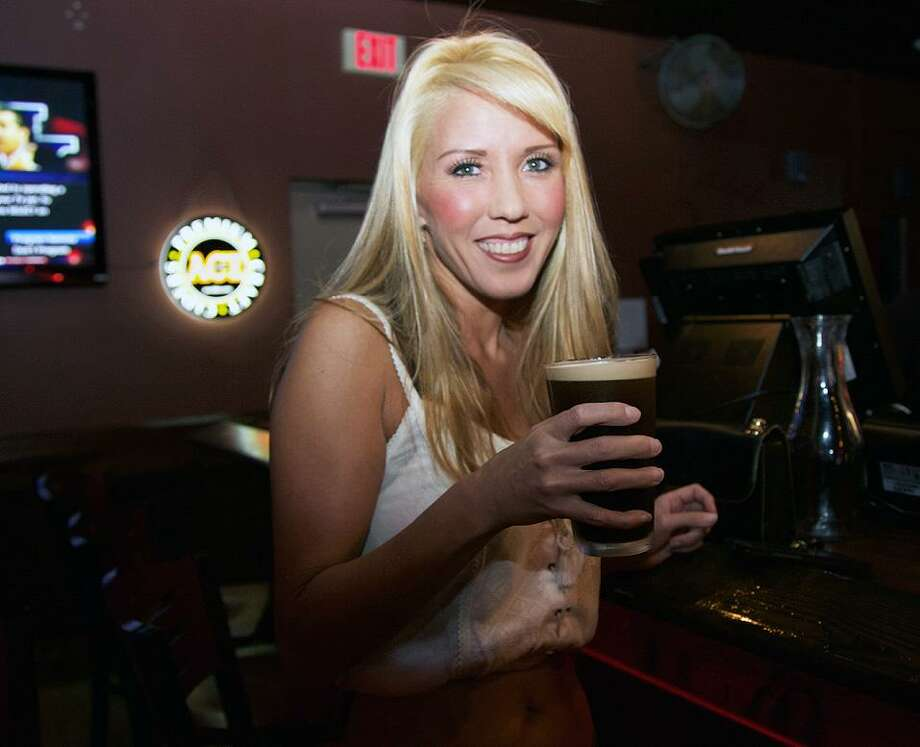 Tania Garcia has a beer at Ricky Bobby's Sports Bar. Photo By: Photo: Xelina Flores /For The Express-News