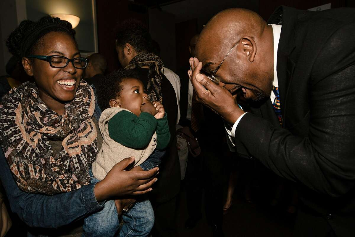 Superintendent Dr. Vincent Matthews plays with Zaire Robinson, 6 months old, held by Mauricha Robinson, 36, at 555 Franklin in San Francisco on March 31, 2017. Ms. Robinson is the African American Parent Advisory Council Cochair for SFUSD.